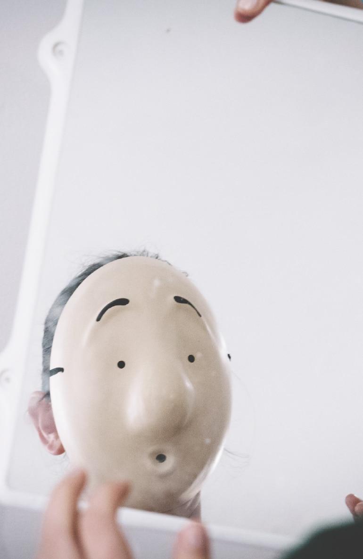אישה חובשת מסכת גולם תמימה ומביטה במראה מתוך האתר של דליה סגל, שחקנית ומנחת קבוצות