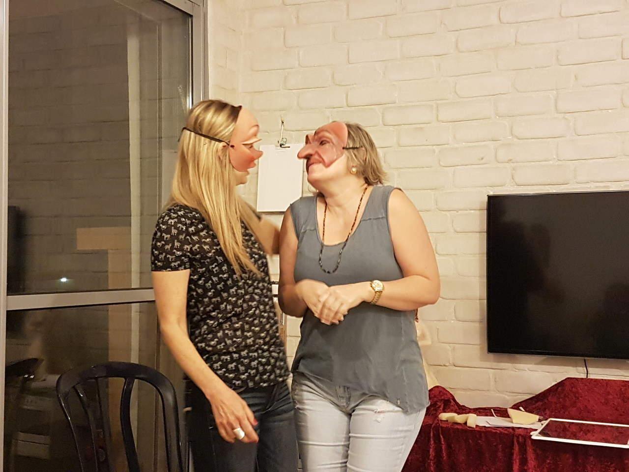 שתי נשים חובשות מסכות תאטרון שונות בסימולציה מתוך הסדנה מאחורי המסכה- מתוך האתר של דליה סגל מנחת קבוצות