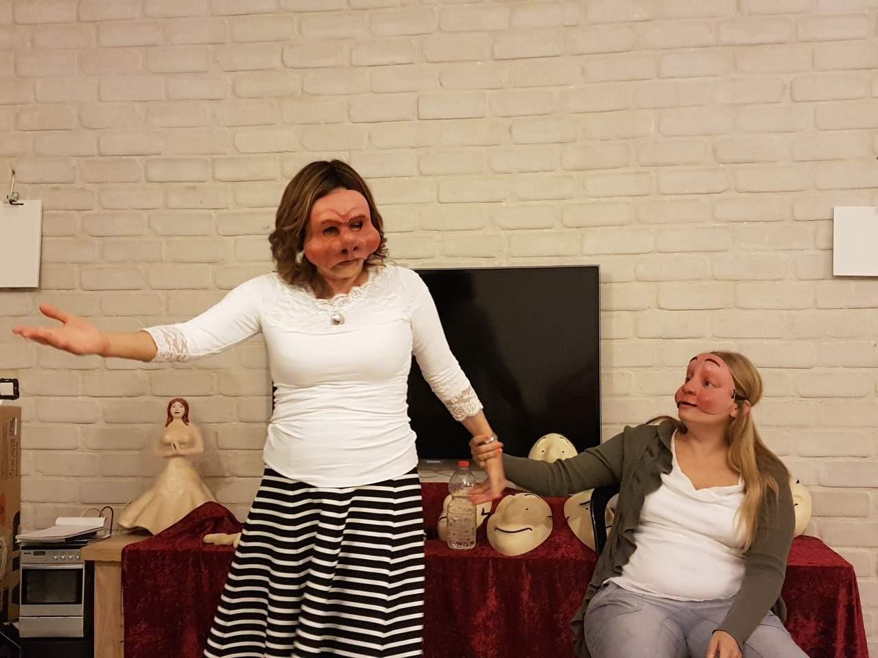 שתי נשים חובשות מסכות תאטרון ומתנסות במשחק תפקידים על שירות ומכירה- מנחה דליה סגל