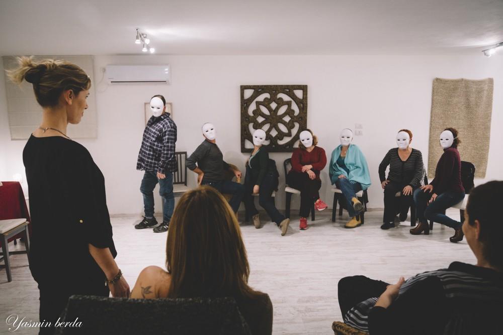קבוצת אנשים במעגל חובשים מסכות ניטרליות(לבנות)- מתוך הסדנה מטחורי המסכה- סדנה על תקשורת בין אישית באמצעות מסכות תאטרון- מנחה דליה סגל